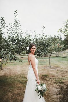 David's Bridal bride Emily in a  spaghetti strap Melissa Sweet gown with a low back and lace, floral applique and a touch of sequins on the bodice for her rustic backyard wedding.