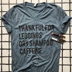 THANKFUL FOR LEGGINGS DRY SHAMPOO AND CAFFEINE Professionally printed with a black ink on a slate blue vneck tee.   Unisex. Size down for a women's fit. Stick with normal size for a looser fit. Do not size up.