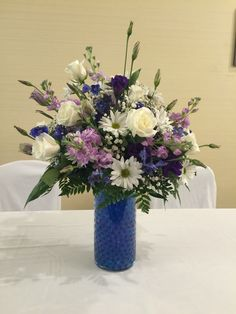 Cylinder centerpiece filled with purple and blue water beads, topped with white roses,lavender stock, purple lisianthus, white daisies, blue delphinium, and babies breath.