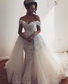 This off the shoulder bridal gown has beautiful embroidery and beading details. The detachable over skirt is flattering. For #fashion forward #weddingdresses like this in a price range you can afford contact us. We are #USA dress #designers who can produce custom #dresses and even #replicas of couture designs for less. We can work from any picture you have to create your dream dress.