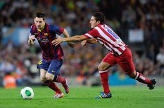 Lionel Messi of FC Barcelona duels for the ball with Koke Resurreccion of Atletico de Madrid during the Spanish Super Cup second leg match between FC Barcelona and Atletico de Madrid at Nou Camp on August 28, 2013 in Barcelona, Catalonia.