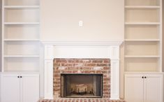 Built in bookcases surrounding a brick fireplace and hearth