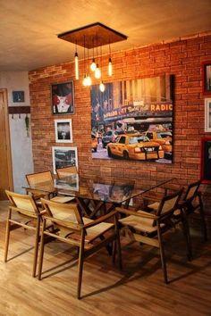 Sala de jantar moderna com parede de tijolinhos, mesa com tampo de vidro, luminária criativa e quadros diversos.