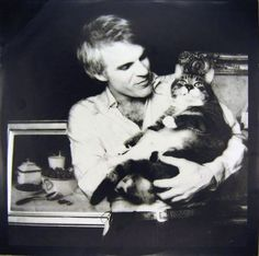 Steve Martin provides carrying services for a cat who is a substantial person and seems appropriately smug