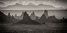 TRONA PINNACLES (Places) - We were leaving Trona Pinnacles after spending the night there when I looked back and saw the hazy morning light striking the landscape in a really magical way. I used the 300mm setting on my lens to compress the pinnacles up against the mountains in the background. I converted the picture to black and white to emphasize the shapes of the pinnacles and their relationship to the mountains