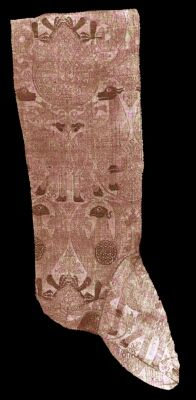 THE ONE TRUE CENTURY: A rare extant 14th century stocking said to have belonged to the archbishop of Bayonne. It is made of a variegated silk brocade, depicting eagles and antelopes, that was woven in the 13th century, and made into a stocking in the following century.