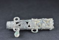 Amlash bronze bead with openworked decoration, 2nd-1st millenium B.C. Amlash bronze bead with openworked decoration with loops for attaching bronze beads, one side round shaped and other triangle shaped, 6.9 cm long, 40.8 gr weight. Private collection
