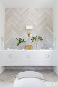 Melanie Turner - Incredible bathroom with gray herringbone tiled accent wall framing gray floating vanity accented with nickel square ring pulls topped with white marble and his and her sinks suspended over herringbone floor.