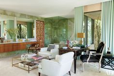 For his Beverly Hills home, photographer Steven Meisel came up with the idea of the hybrid home office/master bath, which is sheathed in green onyx; the teak screen was designed by Brad Dunning, who also decorated the home | archdigest.com