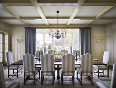 Cream and blue dining room on Martha's Vineyard by Ferguson & Shamamian. Beautiful millwork on the wall and coffered ceiling. Love how the blue is only present on the striped chairs and soft drapes. Formal enough for serious entertaining while being relaxed enough for big family dinners. Summer house perfect.