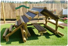 Childrens Playground Log Cabin- what a great design; picnic table built under the climbing wall