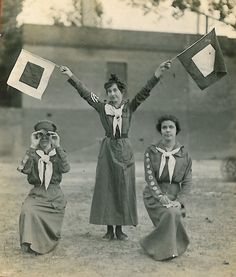 3.13 pm, Friday 13th 1922: the choice of these particular semaphore flags indicates that Edith, Fanny and Gertrude are all single and looking. Fanny has the binoculars, hoping to secure first dibs. (Girl Scouts, ca. 1910)