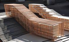 """""""Vivienda en pendiente"""", un edificio que sigue el desnivel del terreno y que esta recubierto por una estructura de listones de madera que tamiza la luz y la visión del interior."""