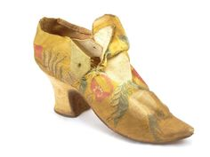 Heeled shoe with a leather sole and soft white leather heel and lining. It has a yellow, white and red silk brocade upper, decorated with a pattern of leaves and fruit. Date: 1700-1710 #shoes #fashion