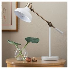 Simple, attractive and there when you need it, the Threshold Crosby Collection Desk Lamp shines its light on what's important. This small lamp is adjustable in 2 places so you can get the perfect position for writing, reading and figuring as long as you need to. The creamy white shade, handle and base pop in contrast with brass hardware for shine and style you can count on.
