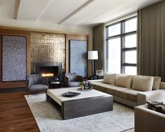 Morgante Wilson Architects designed the custom fireplace surround with sliding doors that hide storage behind.  Leather chairs from WPA offer a cozy place to sit.