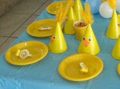 GlitterCoveredMumkids table set up for rubber ducky 1st birthday party yellow party hats with feathers, goggly eyes and orange beak small balloons as bubbles teddy bear taking a bath in duck suit personalised blowouts matching theme of party