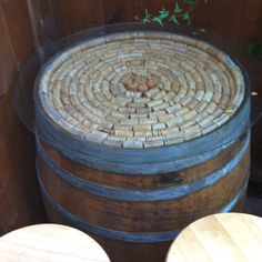 Great idea for bar tables: wine barrels with corks on top and glass table top.
