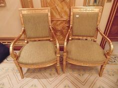 Lot 1 - A pair of Empire style giltwood armchairs the back rest with panelled top rail decorated with