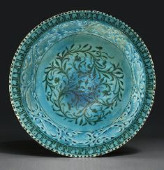 A KASHAN TURQUOISE AND BLACK PIERCED POTTERY BOWL  CENTRAL IRAN, LATE 12TH OR 13TH CENTURY  Of flared conical form on short foot, the interior with a central area of scrolling floral tendrils, the cavetto with a border of scrolling palmettes, the interstices pierced through the body beneath the glaze, the rim with black stylised kufic inscription, the exterior with registers of leafy motif above and below the pierced area, repaired breaks 8in. (20.8cm.) diam.
