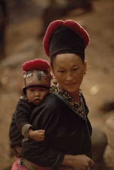 Laos | Portrait of a Hmong woman carrying her child wearing traditional clothes and headdress | © W.E. Garrett #pompom #babywearing #Miao