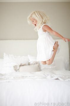 Baby girl jumping on the bed.