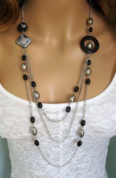 Unique en son genre collier multi-rangs Long noir et argent. Ce Ralston originaux fait à la main collier est fait avec multi brins de chaîne en métal argenté, grande bague acrylique noir, grand argent brosse peint perle noire, grosse perle acrylique noir et argent, perles en acrylique noirs et argent perles en acrylique. Ce collier de perles noir est de 36 pouces de long. Voir tous les colliers dans ma boutique dans une grande variété de STYLES et couleurs au…
