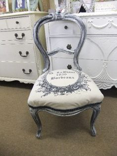 "The shapely petite chair has been distressed with creme, black and grey paint.  It is covered in a grey french print.  The trim is pleated grey velvet.  It measures 19"" wide, 18 "" deep and 16"" from the floor to the seat / 35"" to the top of the back of the chair $295"