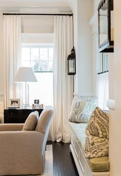 Living Room Window Seat. Living Room Window Seat Flanked by Lantern Sconces. #LivingRoom #WindowSeat #LanternSconces Brookes and Hill Custom Builders.