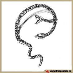 Den tvehodete slange hvisker lokkende ord i øret. . . et spesielt ørepynt med stikk (du må ha hull i øret) og som legges opp og rundt øret som på bildet. Passer til et helt normalt hull i øreflippen, det er en standard stikk-pinne i rustfritt stål som går gjennom selve øret. Passer til høyre øre. Denne ørepynten finnes ikke i venstre-utgave. Materiale: Antikkbehandlet støpetinn. Selve stikket er i rustfritt stål. Mål: ca 62x40mm. Obs at dette er et enkelt smykke.