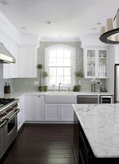 White Marble And Farmhouse Sink - A marbled countertop adds texture to the room