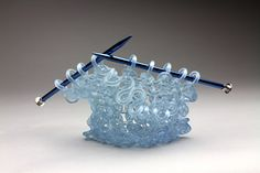 """American artist Carol Milne produces delicate glass sculptures that resemble knitted strands of yarn.  """"Contrary to the assumption that Milne has super-human ability to knit strands of molten glass by hand, the artist instead devised a somewhat complicated process that involves wax casting, mold-making, and kiln-casting.""""  More art on the grid via Colossal"""