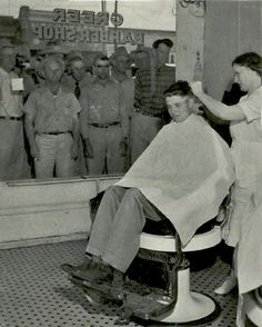 A crowd gathers to watch WWII hero Audie Murphy get a haircut in Farmersville, Texas.  1946.
