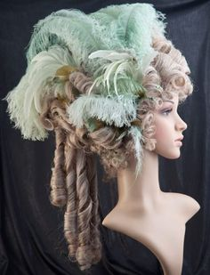 €188,00 EUR. Hair color: gray - blond with golden mica. Ornament color: variations of green. Luxurious lady's wig adorned with decorative feathers and rhinestones. Artificial hair treated with colored and glittering spray.