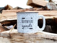 In stock and ready to ship. White with black rim and grey speckled ceramic stoneware mug with black hand lettering and the quote Adventure Awaits: