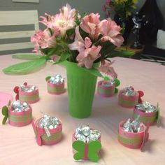 Party favors for girl! Cinnamon roll icing containers wrapped with ribbon using hot glue. Scrapbook paper butterflies and fill with Hershey kisses! Dollar store cups $1 4/pk and $4 for flowers at publix which made 2 centerpieces!