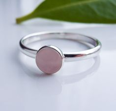 Rose Quartz stacking ring in Sterling Silver.    A 5mm, natural Rose Quartz cabochon stone, is bezel set onto a slim, polished band of Sterling Silver.    The pictures are close up, and magnify slightly for detail.    The Details:  - Rose Quartz is a very pretty stone, said to be the stone of love.  It is also an ancient birthstone for January, and the zodiac sign Aries.  - This is an all natural, 5mm round, smooth Rose Quartz gem stone.  - Set in Sterling Silver  - Aprox 2mm wide, highly…