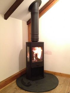 Contura 850 freestanding on a circular hearth wood burning stove installation from Kernow Fires. Wood Burning Logs, Corner Stove, Stove Installation, Wood Burned Signs, Slate Hearth, Rustic Wood Background, Grey Wood Floors, Living Room Wood Floor, Freestanding Fireplace