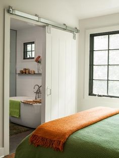 A sliding barn-style door closes off a bath in the master suite. The windows were matched to the 1940 originals.