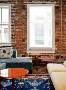 Dieser eklektische Wohnzimmer macht die weiße getrimmte Fenster zur strukturierten Backstein Wand abheben. Foto von Buchanan Fotografie