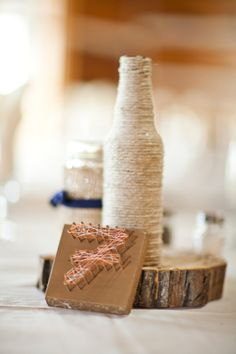 DIY centerpieces with yarn wrapped bottles and handmade table numbers