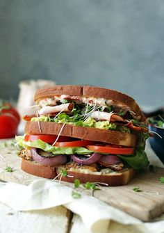 The Ultimate Chicken Club Recipe with marinated and grilled chicken, kale micro-greens, lettuce, tomato, bacon, ham, balsamic roasted onions, mozzarella, avocado and sun-dried tomato basil mayo