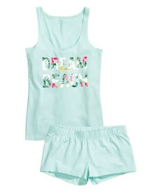 "Soft pastel pajama set with tank top, elastic shorts, and cheeky ""Dream Beach"" tropical print graphic. 