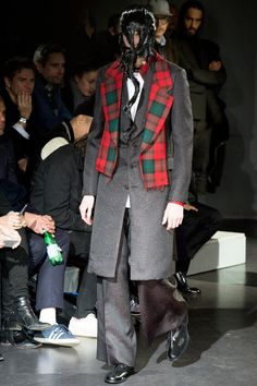 Comme Des Garcons A/W 2014 The lapel and collar have been created separately as an accessory to the jacket. In the tartan print with loose strands is resembles a scarf. The pattern matches the inner collar of the shirt. The overall look questions the purpose of the collar and lapel in regards to the tailored jacket