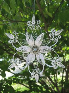 Quilled snowflake with silver beaded detail.