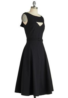 Sleeveless lined black dress with bateau neckline, deeply notched back with white (lining) wings, triangular cutout at bust, front bodice princess darts and side bust darts, matched fabric belt at natural waist, slit pockets, 4-part mid-calf skirt, and back zipper. 65% cotton/35% nylon/5% spandex, by Bettie Page, $129.99 at ModCloth