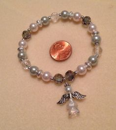 Stretch bracelet with glass pearls, AB clear beads, crystal rondells, and angel charm  $20