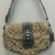 Coach Soho Signature Purse This is a khaki & brown signature coach handbag. It has a top leather buckle flap with magnetic closure, silver hardware, leather Coach hang tag. This bag also has a large outside slip pocket on the back with magnetic closure and a large inside zip pocket along with two medium slip pockets. The bag is in excellent condition (no marks, soiling or stains) and includes the dust bag. Coach Bags