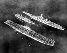 USS Antietam (CV-36) and USS Wisconsin (BB-64) steam alongside USS Rainier (AE-5) as she pulls away after supplying ammunition to the carrier and battleship, in Korean waters, Feb 1952