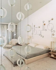 Laid-Back but Luxurious:  This Los Angeles master bedroom features a mix of whimsical elements, such as a metal wall sculpture and a curtain of glass disks; soothing touches, such as translucent silk drapes, provide privacy without obscuring light.